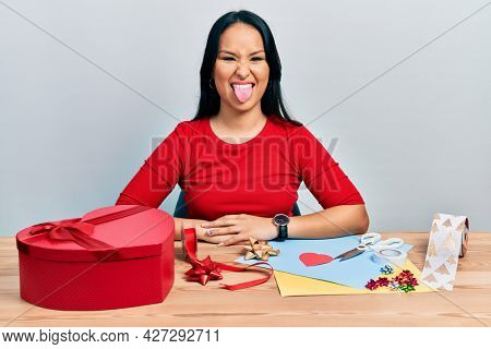 Beautiful hispanic woman with nose piercing doing handcraft creative decoration sticking tongue out happy with funny expression. emotion concept.