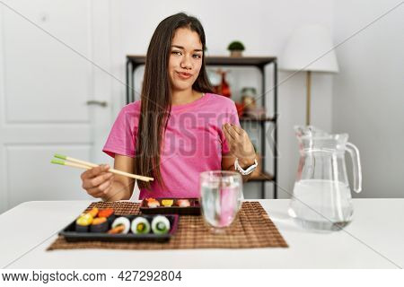 Young brunette woman eating sushi using chopsticks doing money gesture with hands, asking for salary payment, millionaire business