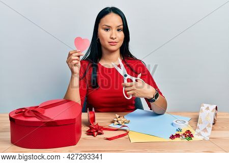 Beautiful hispanic woman with nose piercing doing handcraft heart relaxed with serious expression on face. simple and natural looking at the camera.