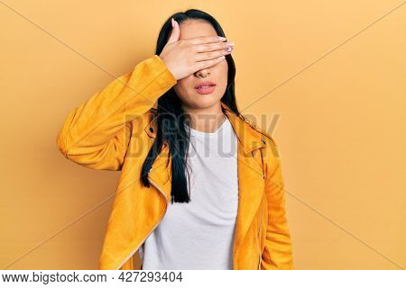 Beautiful hispanic woman with nose piercing wearing yellow leather jacket covering eyes with hand, looking serious and sad. sightless, hiding and rejection concept