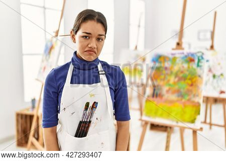 Young brunette woman at art studio looking sleepy and tired, exhausted for fatigue and hangover, lazy eyes in the morning.