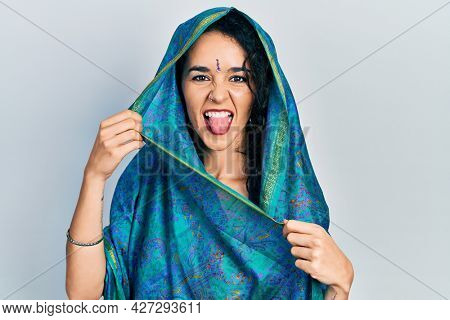 Young woman wearing bindi wearing traditional indian saree smiling with hands on chest, eyes closed with grateful gesture on face. health concept.