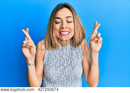 Young caucasian blonde woman wearing casual t shirt gesturing finger crossed smiling with hope and eyes closed. luck and superstitious concept.