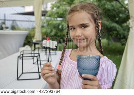 Girl Holding A Glass Of Colorful Natural Fruits Lemonade During Backyard Barbeque Party At Summer, E