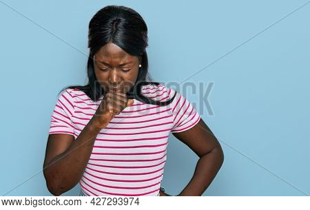 African young woman wearing casual striped t shirt feeling unwell and coughing as symptom for cold or bronchitis. health care concept.