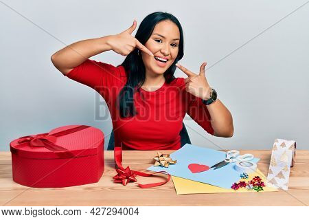Beautiful hispanic woman with nose piercing doing handcraft creative decoration smiling cheerful showing and pointing with fingers teeth and mouth. dental health concept.