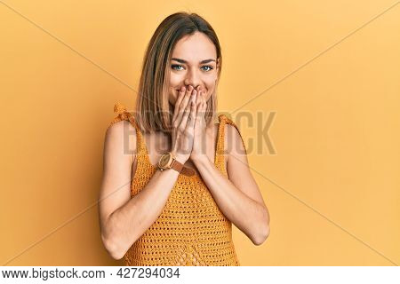 Young caucasian blonde woman wearing casual yellow t shirt laughing and embarrassed giggle covering mouth with hands, gossip and scandal concept