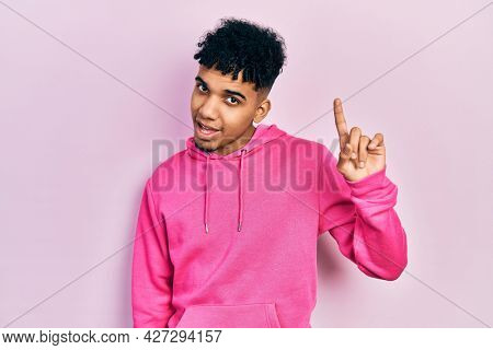Young african american man wearing casual sweatshirt pointing finger up with successful idea. exited and happy. number one.