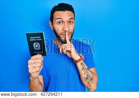 Hispanic man with beard holding italy passport asking to be quiet with finger on lips. silence and secret concept.