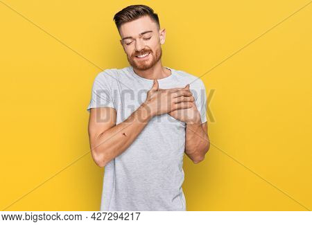 Young redhead man wearing casual grey t shirt smiling with hands on chest with closed eyes and grateful gesture on face. health concept.