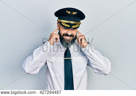 Young hispanic man wearing airplane pilot uniform covering ears with fingers with annoyed expression for the noise of loud music. deaf concept.