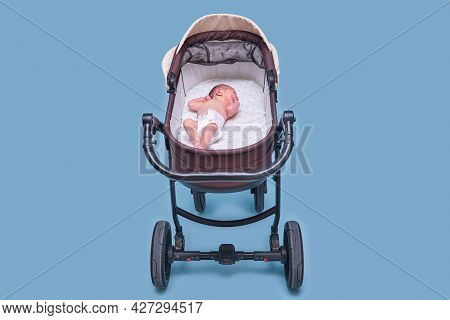 Baby Boy In A Stroller On A Blue Background. A Naked Child In Only Diapers Is Lying In A Stroller, S