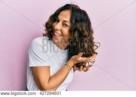 Beautiful hispanic woman curling hair using cosmetics products, doing curly style treatment on hair