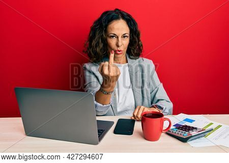 Beautiful middle age woman working at the office drinking a cup of coffee showing middle finger, impolite and rude fuck off expression