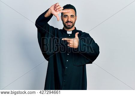 Handsome hispanic man with beard wearing catholic priest robe smiling making frame with hands and fingers with happy face. creativity and photography concept.