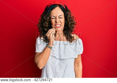 Middle age hispanic woman wearing casual clothes touching mouth with hand with painful expression because of toothache or dental illness on teeth. dentist