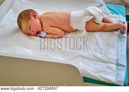 A Newborn Baby With A Maternity Hospital Bracelet On His Arm On A Changing Table