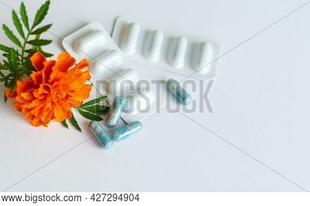 Dietary Supplement Capsules Of Marigold Flowers On White Background. Concept: Vision Improvement, Ey