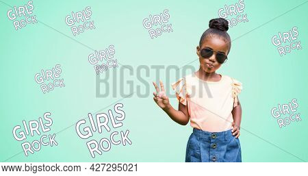 Composition of girl power text over girl with glasses. girl power, positive female strength and independence concept digitally generated image.