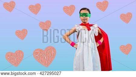 Composition of girl power text over girl in superhero costume. girl power, positive female strength and independence concept digitally generated image.