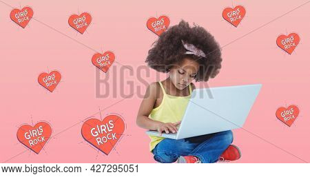 Composition of girl power text over girl using laptop. girl power, positive female strength and independence concept digitally generated image.