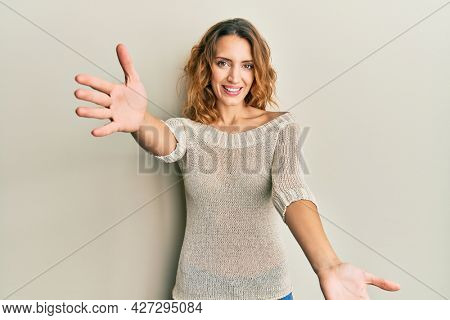 Young caucasian woman wearing casual clothes looking at the camera smiling with open arms for hug. cheerful expression embracing happiness.