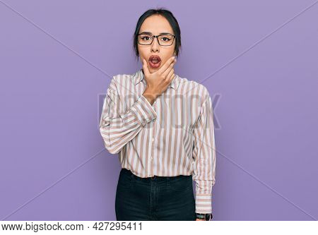 Young hispanic girl wearing casual clothes and glasses looking fascinated with disbelief, surprise and amazed expression with hands on chin