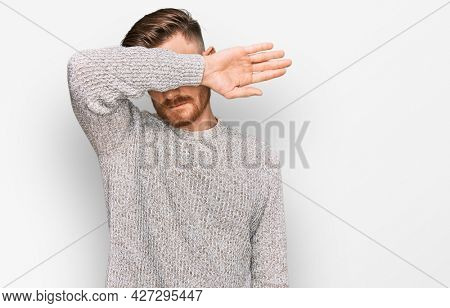 Young redhead man wearing casual winter sweater covering eyes with arm, looking serious and sad. sightless, hiding and rejection concept