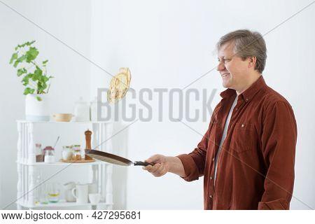 Man Flips  Pancake In  Air In Kitchen