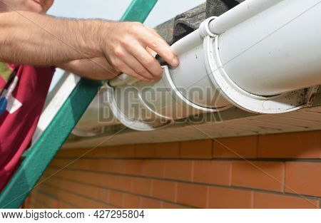Roof Gutter Installation. A Man On A Ladder Is Installing A Roof Gutter's Slip Joint Connector To Co