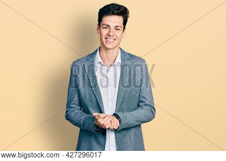 Young hispanic man wearing business clothes with hands together and crossed fingers smiling relaxed and cheerful. success and optimistic
