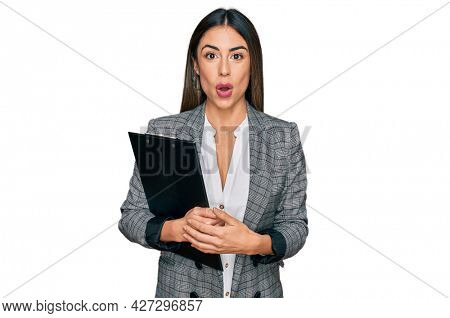Young hispanic woman wearing business clothes holding clipboard scared and amazed with open mouth for surprise, disbelief face