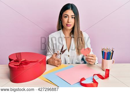 Young hispanic woman making valentine gift sitting on the table relaxed with serious expression on face. simple and natural looking at the camera.