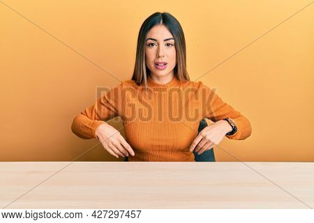 Young hispanic woman wearing casual clothes sitting on the table looking sleepy and tired, exhausted for fatigue and hangover, lazy eyes in the morning.