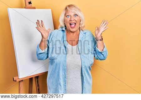 Middle age blonde woman standing by painter easel stand celebrating crazy and amazed for success with arms raised and open eyes screaming excited. winner concept
