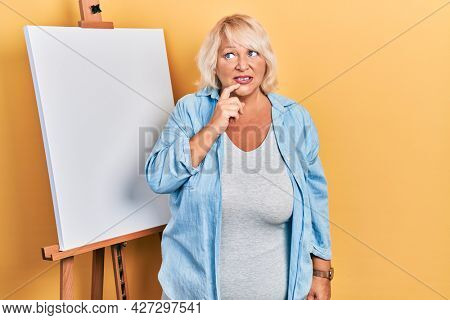 Middle age blonde woman standing by painter easel stand looking stressed and nervous with hands on mouth biting nails. anxiety problem.