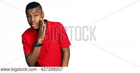 Young african american man wearing casual red t shirt hand on mouth telling secret rumor, whispering malicious talk conversation
