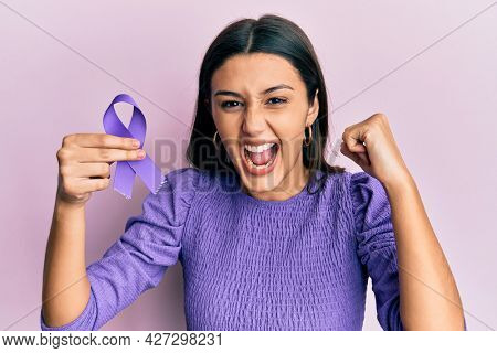 Young hispanic woman holding purple ribbon awareness screaming proud, celebrating victory and success very excited with raised arms