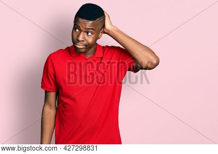 Young african american man wearing casual red t shirt confuse and wondering about question. uncertain with doubt, thinking with hand on head. pensive concept.