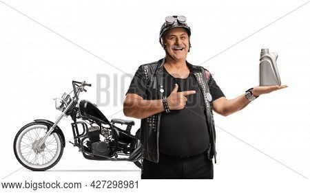 Mature man biker with a chopper holding an engine oil and pointing isolated on white background