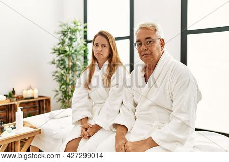 Middle age hispanic couple wearing bathrobe at wellness spa with serious expression on face. simple and natural looking at the camera.