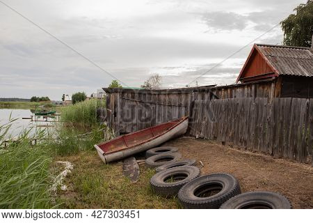 An Old Wooden Boat Sits On The Shore Next To An Old House On The Lake. Old Wooden House On The Shore