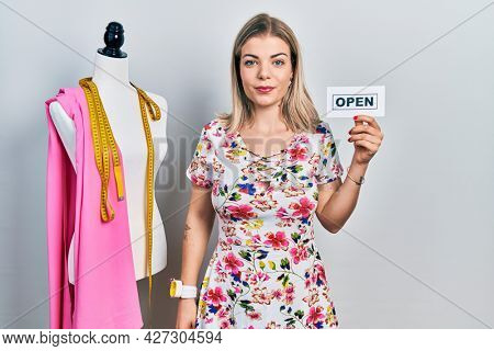 Beautiful caucasian woman dressmaker designer holding open sign thinking attitude and sober expression looking self confident