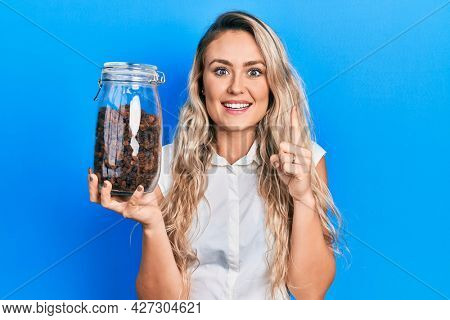 Beautiful young blonde woman holding raisins bowl smiling with an idea or question pointing finger with happy face, number one