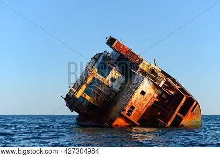 The Rusting Remains Of The Hull Of A Stranded Ship In The Open Sea