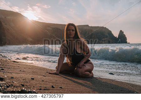 Selective Focus. Happy Carefree Sensual Woman With Long Hair In Black Swimwear Posing At Sunset Beac