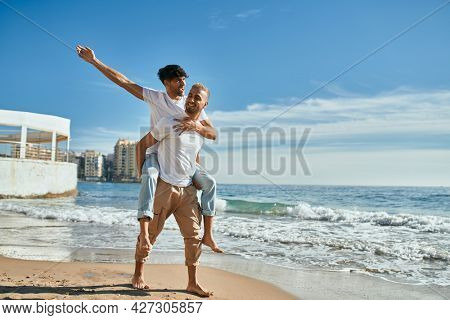Lovely gay couple on piggyback ride at the beach.
