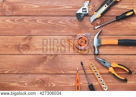 Set Of Construction Tools On A Wooden Background. Hammer, Wrench, Pliers And Screwdriver. Frame For