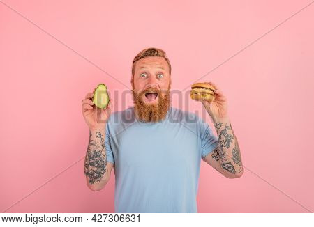 Amazed Man With Beard And Tattoos Is Undecided If To Eat An Avocado Or An Hamburger