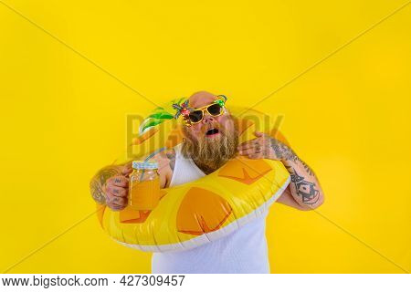 Fat Annoyed Man With Wig In Head Is Ready To Swim With A Donut Lifesaver